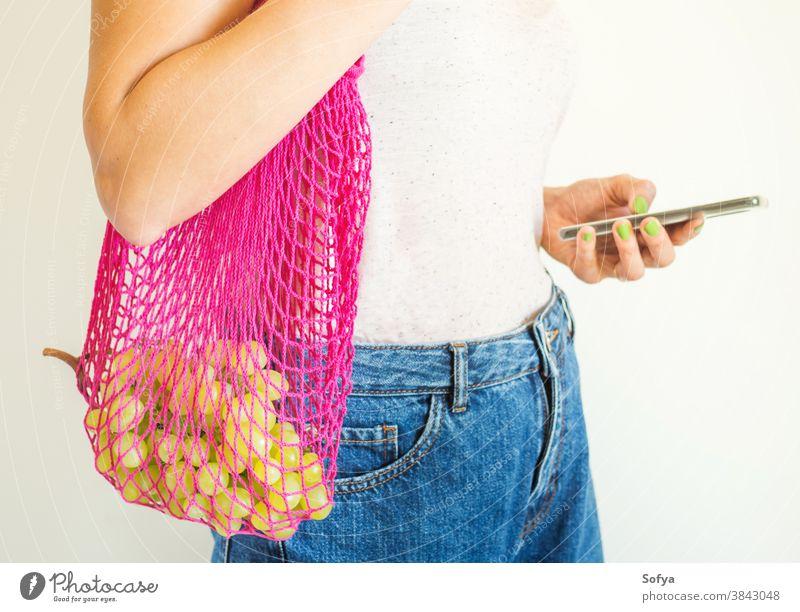 Junge Frau mit wiederverwendbarer Netztasche und Smartphone Tasche ineinander greifen Lebensmittel benutzend Handy online Versand Lebensmittelgeschäft Frucht