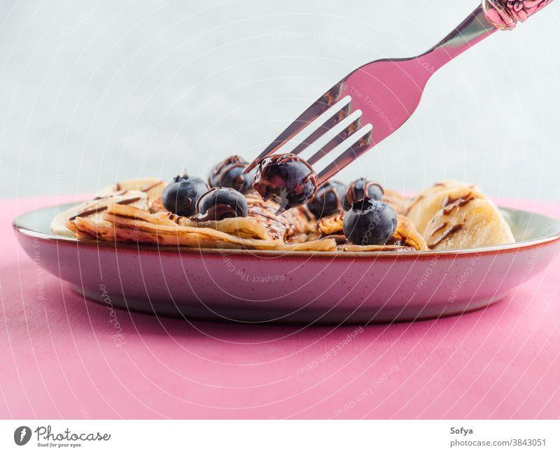 Crêpes mit Schokolade und Heidelbeeren essen Banane Haselnuss Gabel Kronleuchter rosa süß Frühstück Nahaufnahme Aufstrich Maslenitsa serviert Pfannkuchen
