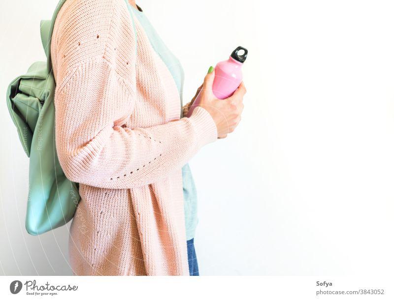Frau in Pastell mit Rucksack und wiederverwendbarer Flasche rosa Wasser Lifestyle keine Verschwendung trinken Mode Öko Nachfüllen frei Konzept Hipster Tasche