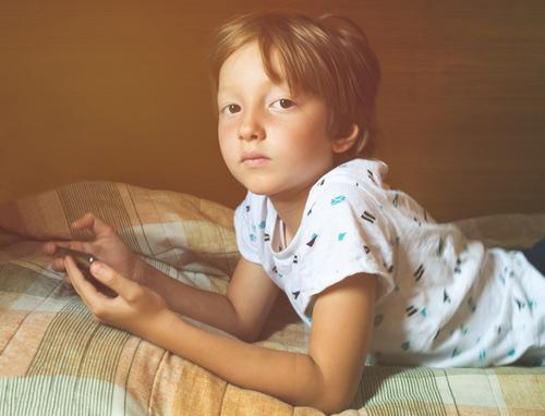 Kleiner blonder Junge spielt Spiele am Smartphone Kind spielen allein Mobile benutzend App Apparatur digital zuschauend Bildschirm Gerät Schule Spaß heimwärts