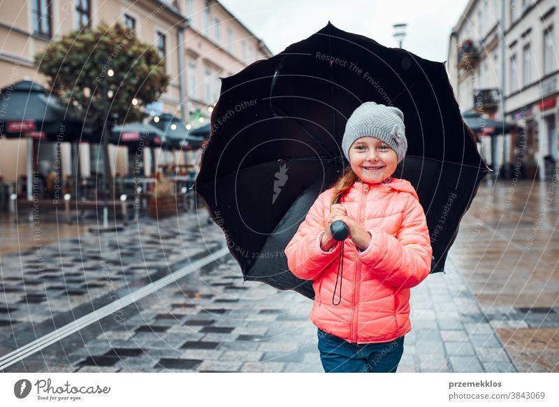 Kleines Mädchen mit großem Regenschirm in der Hand geht an einem verregneten, düsteren Herbsttag durch die Innenstadt im Freien wenig saisonbedingt fallen