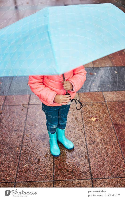 Kleines Mädchen hält großen blauen Regenschirm beim Spaziergang an einem regnerischen Tag regnet im Freien heiter freudig wenig Herbst saisonbedingt fallen