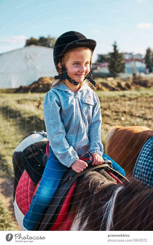 Kleines lächelndes Mädchen lernt Reiten Kind Mitfahrgelegenheit Pferd üben Schule niedlich Land hübsch ländlich Ranch Lektion Reiter Fröhlichkeit lernen