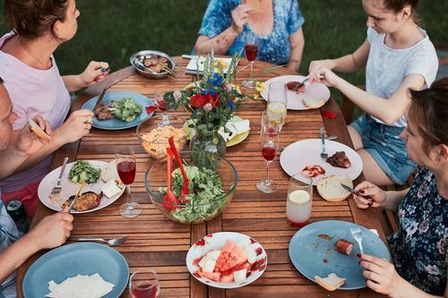 Familie isst während des Sommerpicknicks im Freien in einem Hausgarten zu Abend heimwärts Festessen habend Picknick Lebensmittel Mann Zusammensein Frau Kind