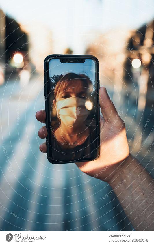 Junger Mann führt Videogespräch, während er mit der Gesichtsmaske in der Innenstadt läuft, um eine Virusinfektion zu vermeiden Anruf Pflege Kaukasier Talkrunde