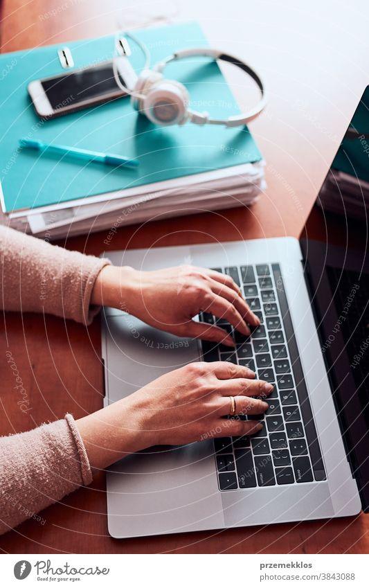 Frau, die während eines Videochat-Telefongesprächs mit einem Laptop von zu Hause aus arbeitet und dabei ihre Arbeit aus der Ferne erledigt Ordner Anruf