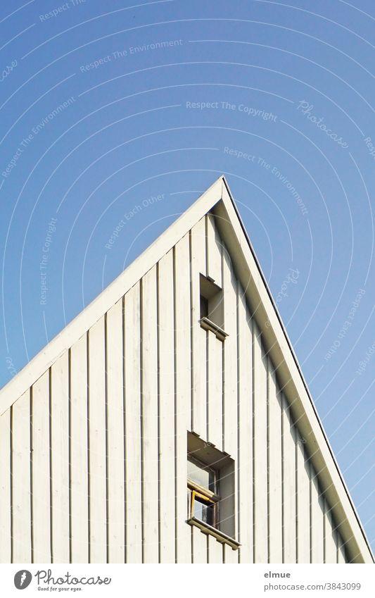 raffiniert gestalteter Hausgiebel in weißem Holz mit zwei Fenstern vor blauem Himmel / optische Täuschung Giebel wohnen Gebäude Fassade Wohnung Architektur