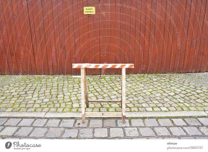 """Ein Arbeitsbock aus Holz steht teils auf der Straße, teils auf dem Fußweg vor einem dichten, rot-braunen Holzlattenzaun mit einem gelben Schild """"Ausfahrt freihalten!"""""""