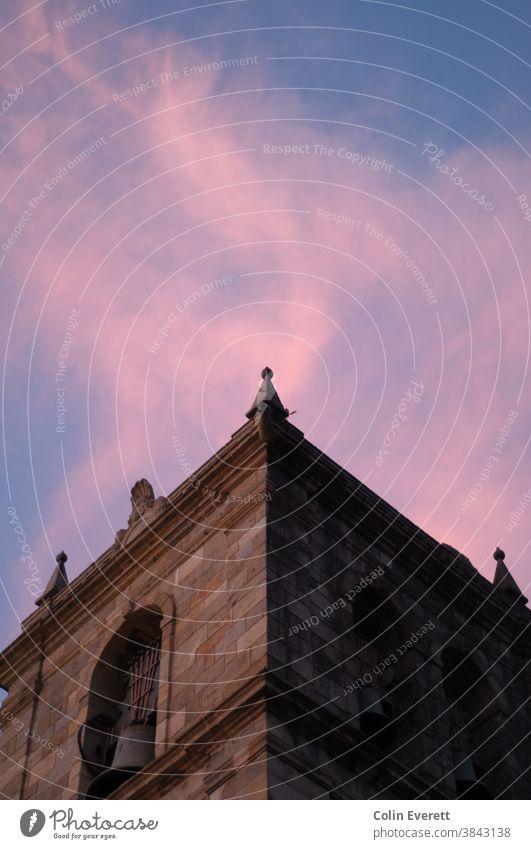 Rosa Sonnenuntergang hinter dem alten Glockenturm der Kirche Kirchturmspitze Religion & Glaube Turm Wolken Farbfoto Architektur Außenaufnahme Bauwerk historisch