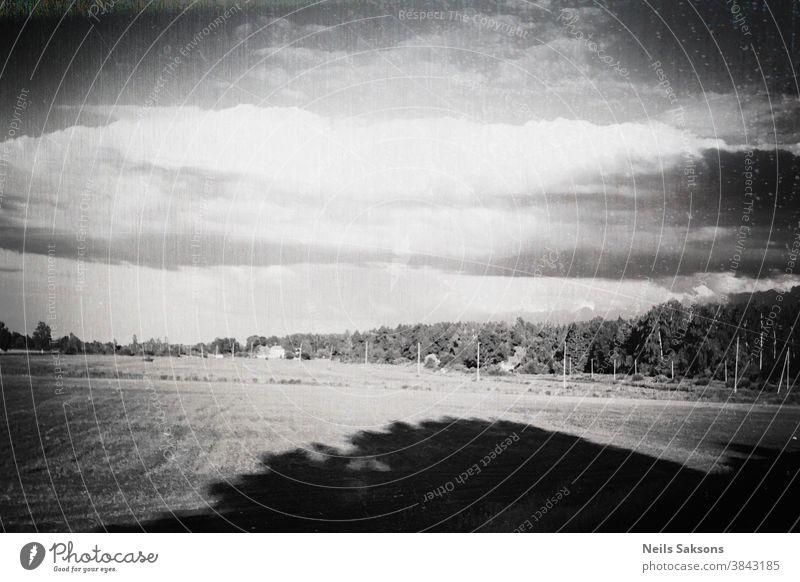 schäbige Landschaft mit großem Baumschatten und massiver dunkler Vignette. schiefer Horizont. gealtert Lettland lettisch Hintergrund Tag wüst leer berühmt
