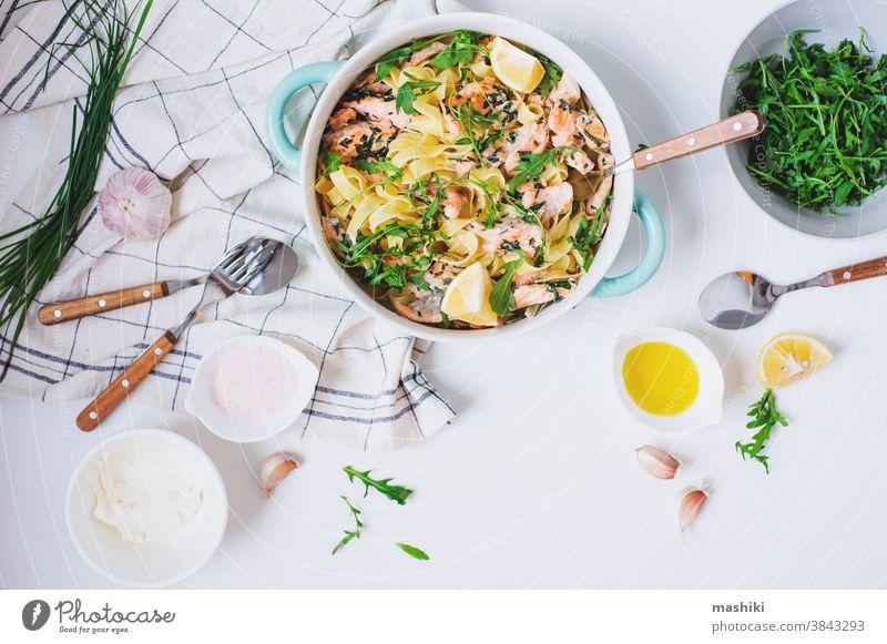 Italienische Küche - cremige Lachsnudeln mit Rucola, Spinat und Käse, serviert mit Zitrone Lebensmittel Spätzle Abendessen Fisch Mittagessen Saucen Gesundheit