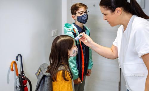 Mutter kontrolliert die Temperatur ihrer Tochter vor dem Schulbesuch Thermometer Überprüfung Fieber Coronavirus Schutzmaske heimwärts Familie im Innenbereich