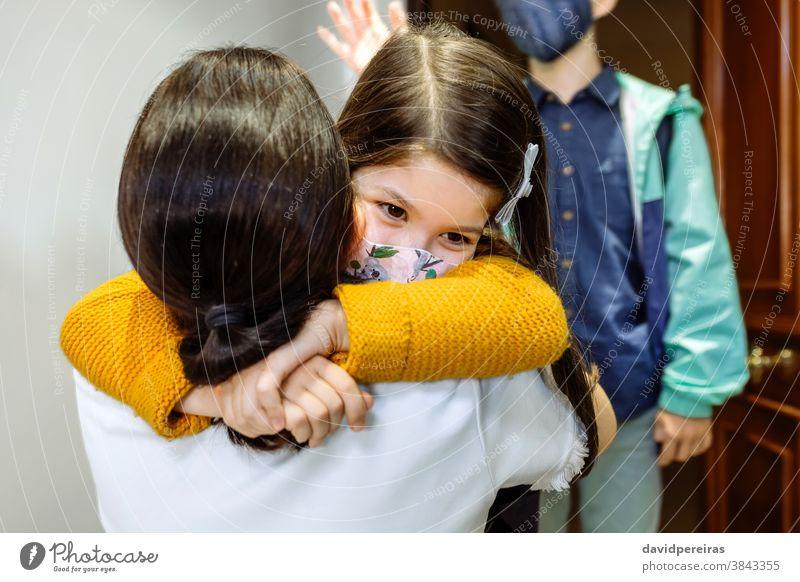 Mutter umarmt Tochter mit Maske, die von der Schule zurückkommt umarmend danach Schutzmaske covid-19 vorher Coronavirus Sohn Mädchen Sicherheit jung Kind
