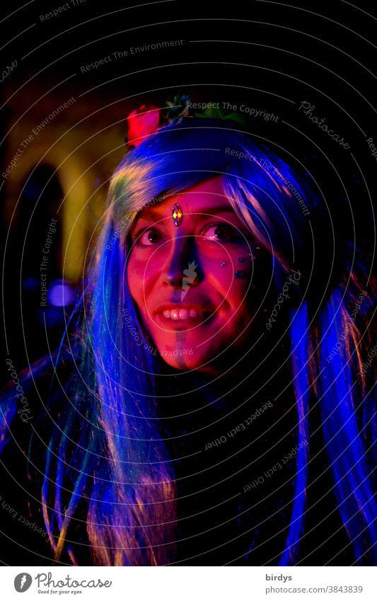 geschminkte schöne junge Frau mit langen Haaren in buntem Licht . Nachtaufnahme, Portrait Porträt gesicht Schönheit farbenfroh attraktiv Gesicht Lächeln