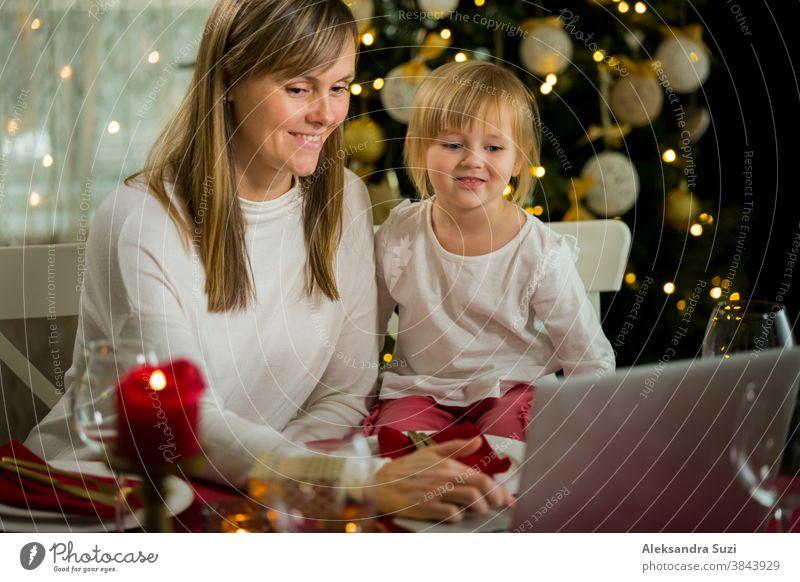 Eine glückliche Familie mit einem Kind feiert Weihnachten mit ihren Freunden per Videoanruf per Webcam. Die Familie begrüßt ihre Verwandten am Heiligabend online. Neue normale virtuelle Veranstaltung