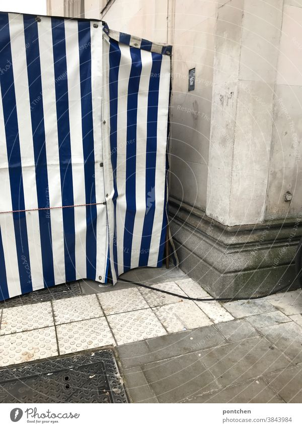 Ein Blau-weiß gestreifter Obststand von der Seite. Plane, Zelt, Obsstand plane plastik Streifen stromkabel Muster Abdeckung Kunststoff Schutz Menschenleer