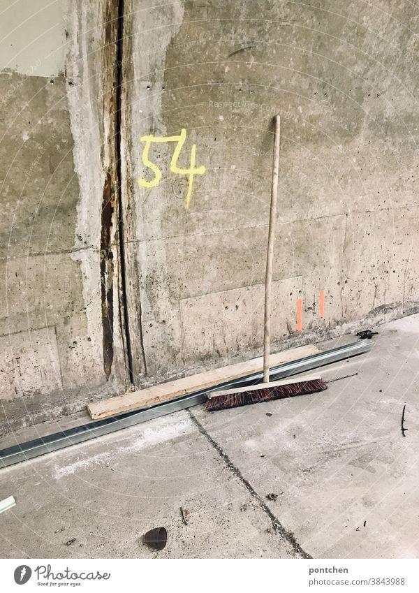 Ein Besen lehnt an einer Betonwand.  Baustelle. Die Zahl 54 steht auf einer Wand. Markierung baustelle beton Reinigen dreckig Menschenleer
