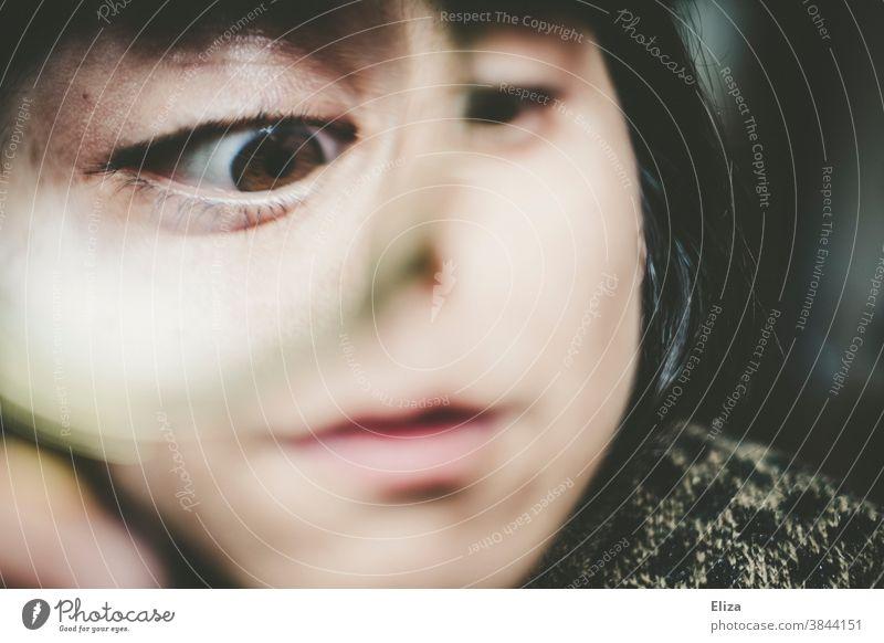 Verzerrtes Gesicht einer Frau, die mit dem Auge durch eine Lupe guckt verzerrt lustig schielen schräg Grimasse Blick neugierig vergrößert Linse