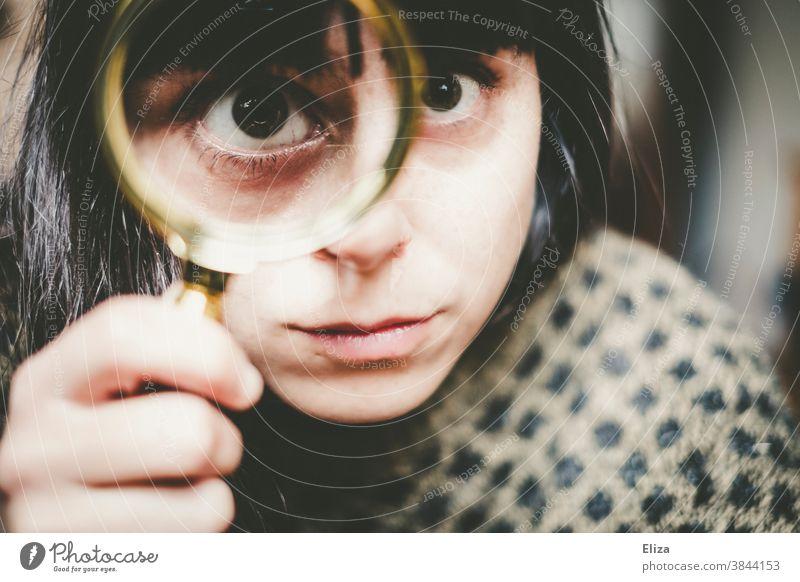 Junge Frau guckt durch eine Lupe genauer hin. hinsehen vergrößert Auge untersuchen prüfen schielen verzerrt Gesicht Linse Blick Detektiv Neugier beobachten