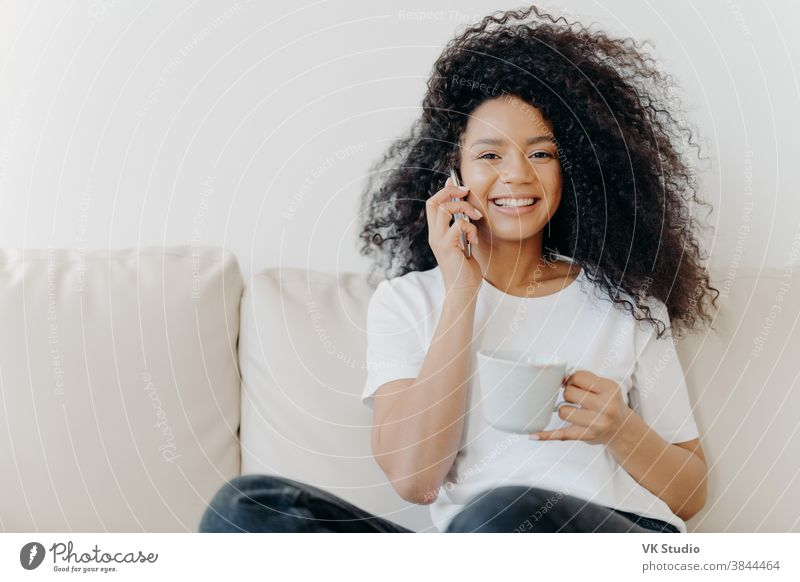 Horizontale Aufnahme einer gut aussehenden Frau, die ein Ferngespräch per Mobiltelefon führt, während des Gesprächs informelle Fragen löst, im Wohnzimmer auf dem Sofa sitzt, Tee trinkt, ein breites Lächeln hat, weiße Zähne zeigt