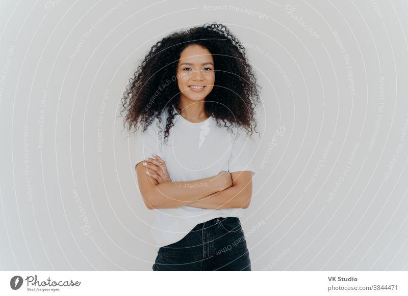 Studioaufnahme einer unbekümmerten jungen, schönen Frau mit Afro-Frisur, die die Arme verschränkt hält, fröhlich lächelt, lässiges T-Shirt und Jeans trägt, isoliert auf weißem Hintergrund. Menschen, Ethnizität, Gesichtsausdrücke