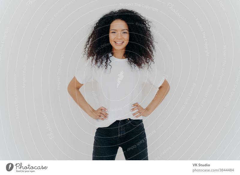 Foto einer entzückten gelockten Frau, die beide Hände in der Taille hält, sanft lächelt, eine schlanke Figur hat, ein weißes T-Shirt und schwarze Jeans trägt, gut gelaunt ist, selbstsicher vor weißem Hintergrund steht
