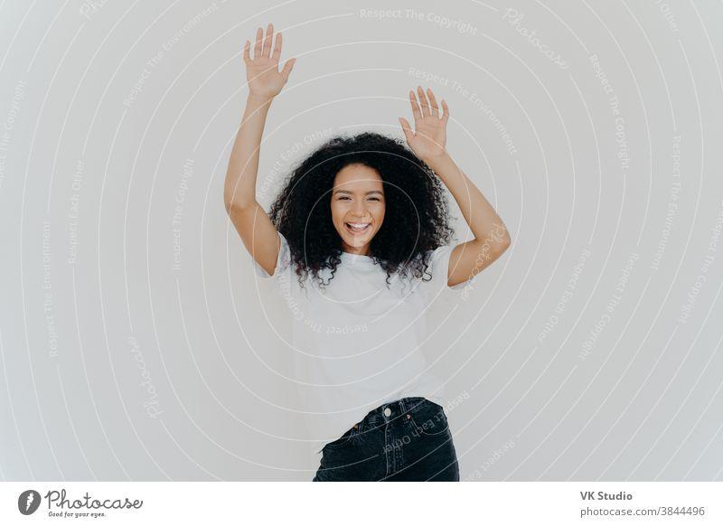 Halbe Einstellung einer energischen, sorglosen, lockigen Frau, die mit erhobenen Händen jubelt, weißes T-Shirt und Jeans trägt, Glückstag hat, perfektes Wochenende, Models vor weißem Hintergrund. Alle nehmen die Hände hoch