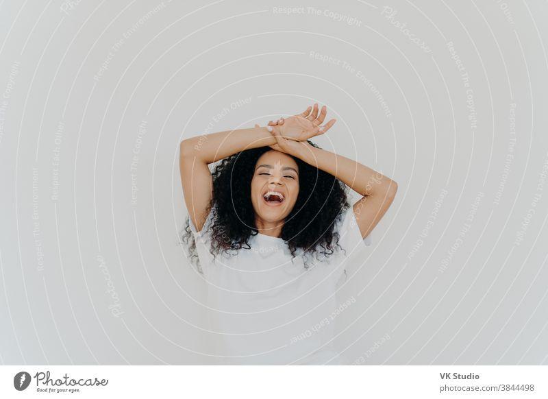 Überglückliche, lockig behaarte junge Dame hält beide Hände auf der Stirn, öffnet den Mund und lacht fröhlich, fühlt sich energisch, in Freizeitkleidung gekleidet, posiert vor weißem Studiohintergrund. Was für ein lustiger Witz!