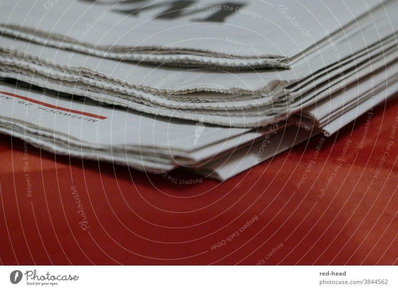 Nahaufnahme von Tageszeitung, obere Kante, aur rotem Untergrund, nur eine Ecke und Falz sichtbar Zeitung Papierstapel weiß