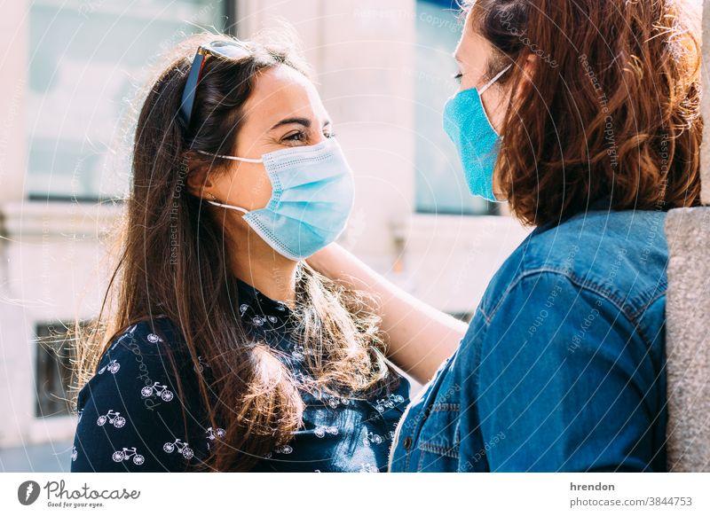 Paar Frauen mit Gesichtsmaske, die sich auf der Straße umarmen lesbisch Homosexualität Coronavirus Liebe Bund 19 Freundin Glück umarmend Lifestyle Romantik