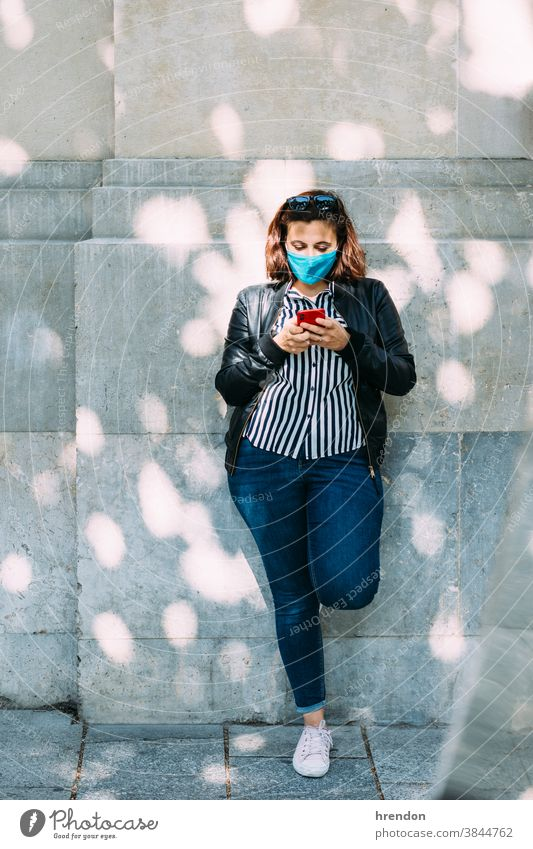 Frau mit einer Gesichtsmaske, die mit ihrem Smartphone an der Wand lehnt jung Telefon Lifestyle Lehnen Internet Mitteilung Technik & Technologie Mobile