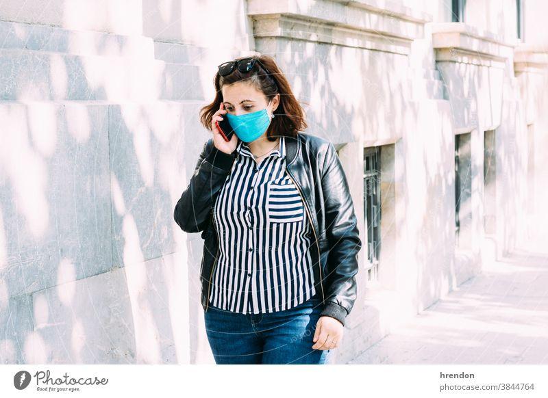 Frau mit Gesichtsmaske telefoniert, während sie die Straße entlang läuft laufen Coronavirus Sicherheit Person sprechend Erwachsener Mitteilung im Freien Handy