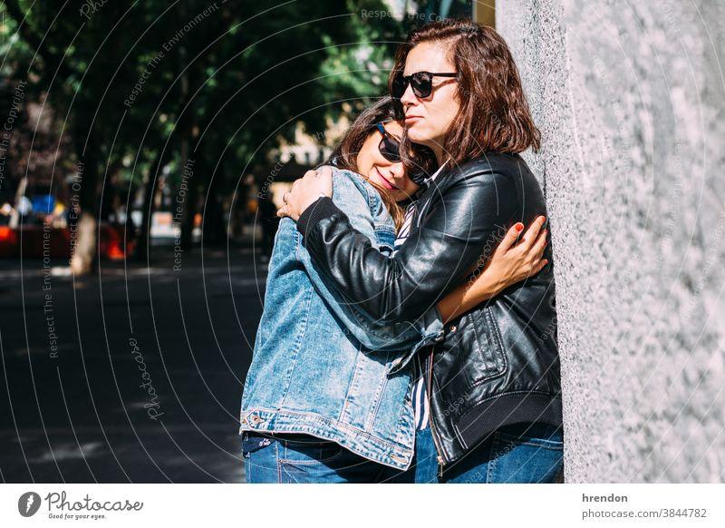 Frauenpaar, das sich auf der Straße umarmt lesbisch Paar Liebe Homosexualität im Freien Freundin Glück umarmend Lifestyle anhänglich Romantik