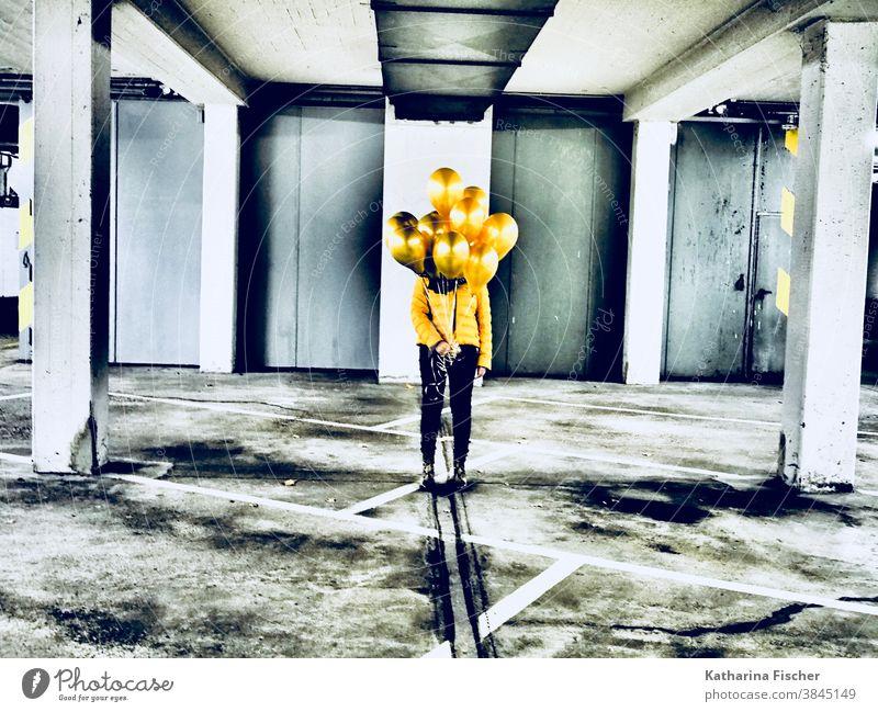 Goldene Luftballons gelb Ballons Farbfoto Farbe Tiefgarage grau weiß schwarz gold gelbe Jacke schwarze Hose unterirdisch Linie Parkhaus parken Kunst stehen
