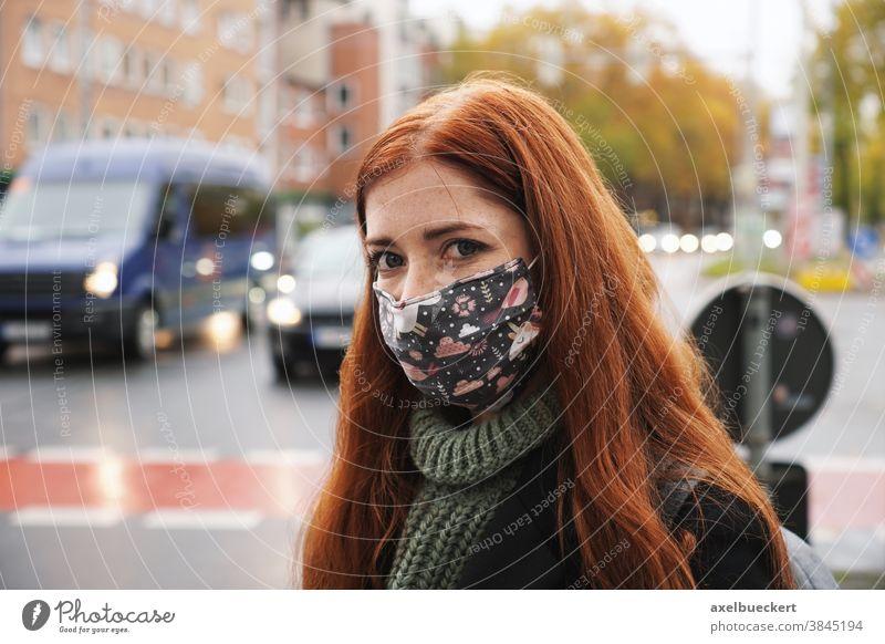 junge Frau, die im Stadtverkehr eine Alltagsmaske trägt Mundschutz Gesichtsmaske Straße Verkehr Winter echte Menschen Gemeinschaftsmaske Stoff Lifestyle