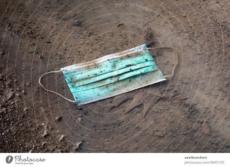 weggeworfene gebrauchte Einweg-Maske, die in einer Pfütze am Boden liegt mund-nasen-schutz Mundschutz Gesichtsmaske Umweltverschmutzung Einwegartikel covid-19