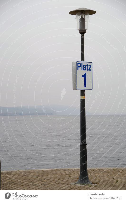 laterne mit schild platz 1 am fähranleger in uhldingen am bodensee angeschraubt weiß Hinweisschild Schriftzeichen Tag Zeichen Menschenleer Außenaufnahme