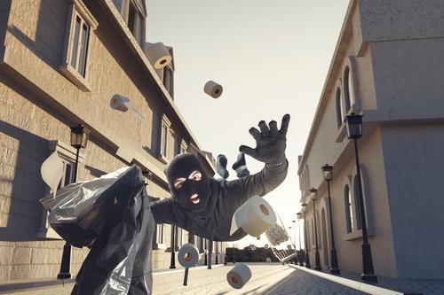 tollpatschiger Dieb mit fliegenden Toilettenpapierrollen stürzt zu Boden Unfall Gasse Sturmhaube Bandit überrascht gestohlen Panik Gebäude Einbrecherin gefangen