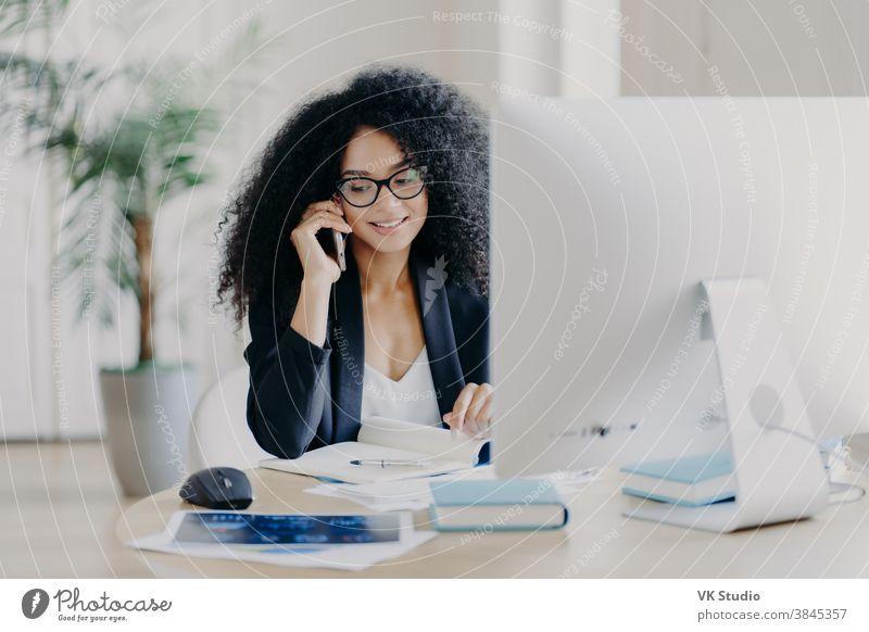 Foto einer zufriedenen Afroamerikanerin, die per Smartphone telefoniert, Notizen im Notizblock macht, am Arbeitsprozess beteiligt ist, am Schreibtisch mit Computer sitzt, eine Brille trägt, formelle Kleidung trägt, telefoniert