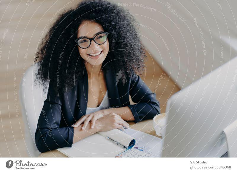 Draufsicht der frohlockenden afroamerikanischen Geschäftsfrau lächelt angenehm, notiert Informationen, macht Notizen, trägt durchsichtige Brille, formelle Kleidung, Computermonitor vorne, sitzt allein am Schreibtisch