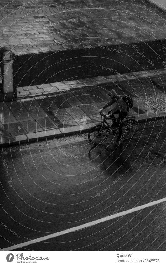 Mann fährt Fahrrad im starken Regen Fahrradfahren Fahrradtour Verkehr Verkehrsmittel Sommerregen Gewitter Gewitterregen Rucksack Wassertropfen Tropfen nass