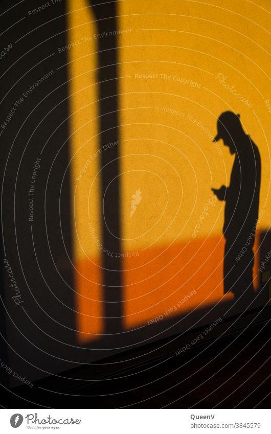 Schatten eines Mannes mit Handy Kommunikation orange Wand Telefon Lifestyle Mobile Technik & Technologie Internet modern Jugendliche Baseballmütze Gerät