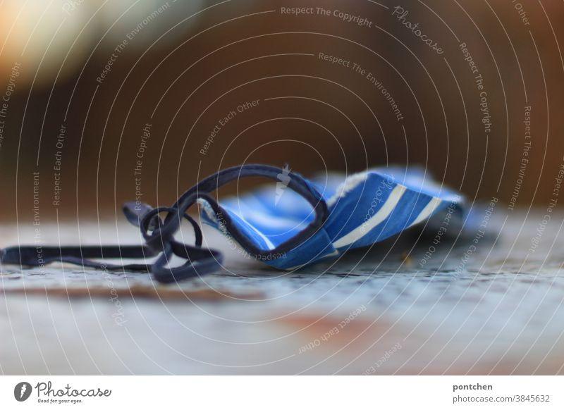 Eine atemschutzmaske, alltagsmaske liegt im Freien auf einem Tisch. Maskenpflicht. Corona Atemschutzmaske covid-19 maskenpflicht gesundheitsschutz mundschutz