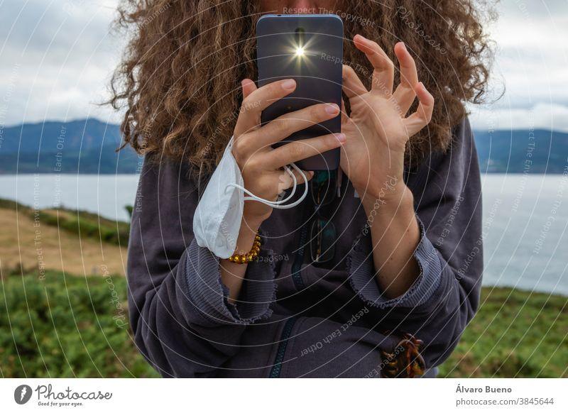 Eine junge Frau, die nach einer Gesichtsmaske und einem intelligenten Mobiltelefon greift, Spanien. Telefon Mädchen Behaarung lockig schützend Mundschutz neu