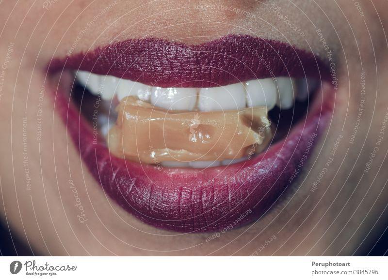 Nahaufnahme eines Frauenmundes, der in Karamellbonbons beißt Bonbon Mund Lebensmittel Lippen rot Mädchen Person geschmackvoll Zähne jung Biss sexy rosa
