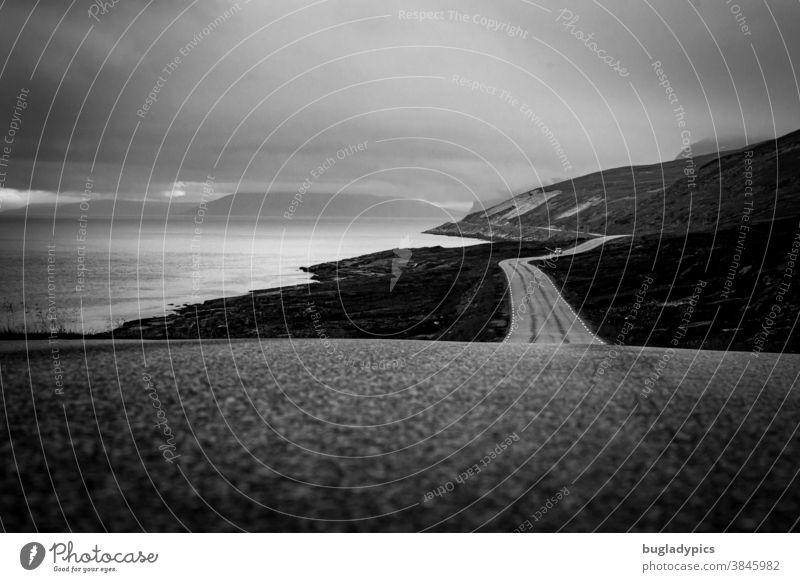 Einsame gewundene Küstenstraße auf der nur in der Ferne einAuto zu sehen ist. Links liegt der Fjord/ das Meer und rechts und im Hintergrund Berge. Der Himmel ist wolkenverhangen und trüb.