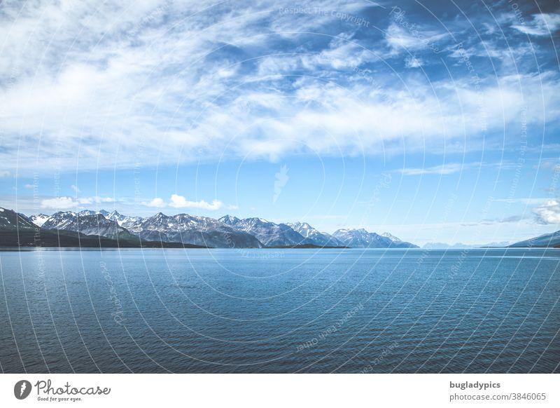 Ein Fjord in Norwegen. Im Vordergrund das Meer und im Hintergrund schneebedeckte Berggipfel. Den blauen Himmel zieren Schleierwolken. Küste Berge u. Gebirge
