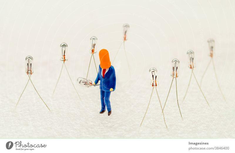 Miniatur Glühlampen und Miniaturfigur mit Kappe, die eine Glühbirne hält. minimal abstrakt Kreatives Ideenkonzept Subminiatur 12v Allee Hintergrund Hintergründe
