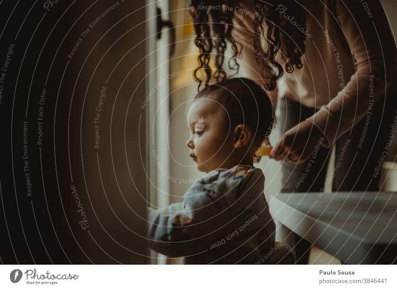 Mutter mit Kind am Fenster 0-09 Jahre 30-39 Jahre lernen Lernen und Wissen anhänglich zu Hause authentisch fürsorglich lässig Kaukasier Farbe Neugier