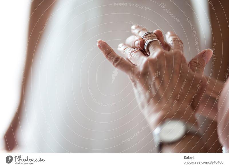 Ältere Frau steckt sich einen Ring an den Mittelfinger anstecken Schmuck Hand Alt Finger feminin wertvoll kostbar Moment Accessoire elegant